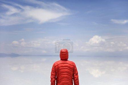 Young man in winter hooded jacket at Salar de uyuni salt flat in Bolivia
