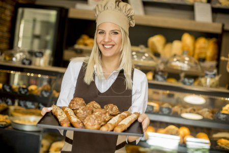 Photo for Beautiful female bakery posing with various types of pastries and breads in the bakery - Royalty Free Image