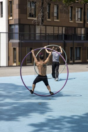 NEW YORK, USA - AUGUST 27, 2017: Unidentified Cyr wheel gymnasts on the street in New York City. Cyr wheel was reinvented and developed as a circus apparatus by Daniel Cyr at 1996.