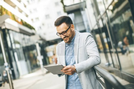 Photo for Handsome young businessman with digital tablet by the office building - Royalty Free Image