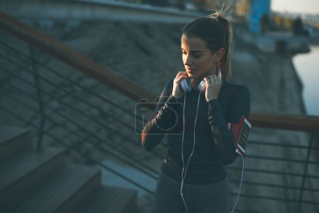Attractive young female runner taking break after jogging outdoors