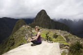 Young woman meditating above Machu Picchu Inca citadel in Peru