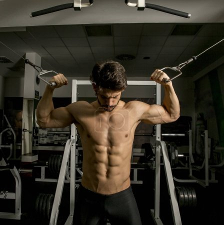 Half-naked muscular man in gym doing exercises for biceps