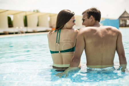 Young couple relaxing by the swimming pool on a sunny day