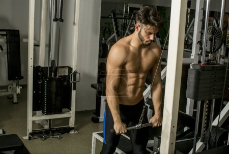 Photo for Naked torso muscular man working out in gym doing triceps exercises - Royalty Free Image