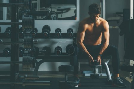 Portrait of strong and handsome young man doing exercise with dumbbells