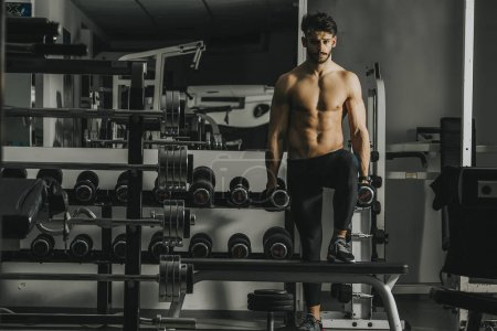 Handsome young man training in the gym
