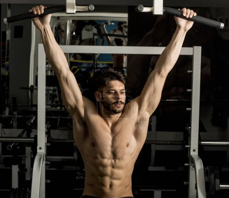 Half-naked young man doing pull ups in the gym