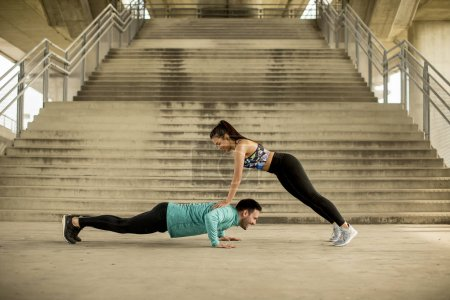 Athletic young couple doing stretching  exercises together outdoor