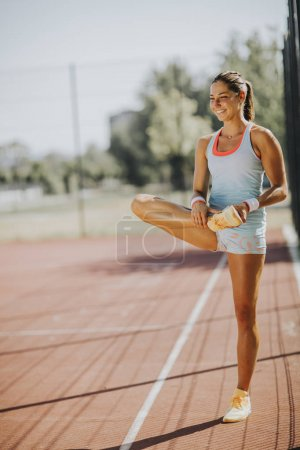 Sporty woman exercising stretching legs before training