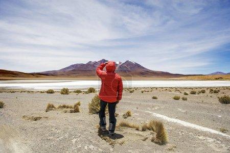 Young man lookinag at lagoon and mountains at Eduardo Avaroa Andean Fauna National Reserve in Bolivia