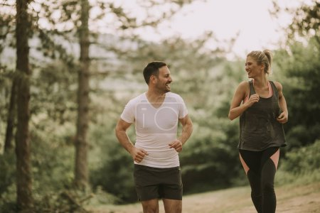 Photo for Young couple jogging outdoors in nature - Royalty Free Image
