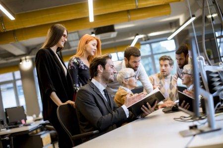 Photo pour Une femme d'affaires de haut niveau travaille avec des jeunes entrepreneurs dans un bureau moderne - image libre de droit