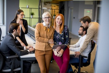 Photo for Happy business women working together online on a digital tablet in front of young team at the office - Royalty Free Image