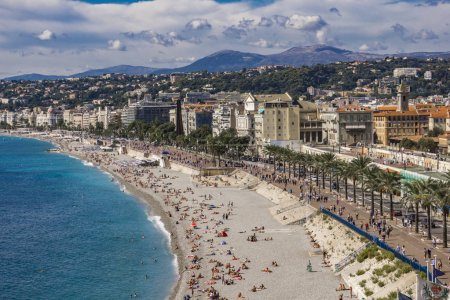 Photo for NICE, FRANCE - OCTOBER 6, 2019: Unidentified people on the beach and the Promenade des Anglais at French Riviera in Nice, France. In nie there are 15 private and 20 public beaches. - Royalty Free Image