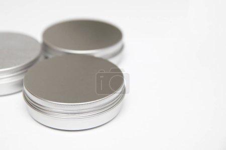 Photo pour Baume à lèvres dans les boîtes métalliques rondes isolées sur le fond blanc - image libre de droit