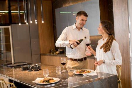 Photo pour Jeune couple sucré prenant un dîner romantique dans une cuisine de luxe - image libre de droit