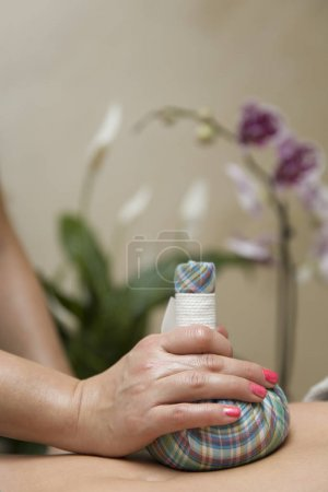 Photo pour Femme ayant un massage de l'abdomen avec des sacs aromatiques à base d'herbes dans le salon cosmétique - image libre de droit