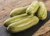 Fresh zucchini on wooden background