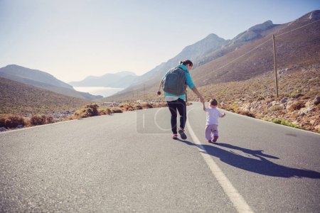Woman and daughter walking down road