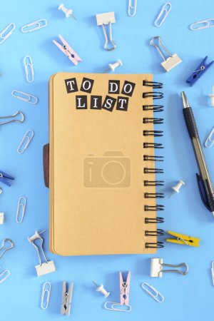 Notepad on springs with an inscription on the open page.To do list. The stationery is in disarray. Blue background.