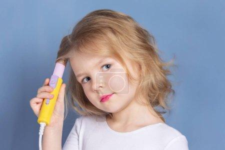 Photo pour Petite fille aux cheveux blonds rend le style. L'enfant tient des fers à friser. Photographie publicitaire lumineuse . - image libre de droit