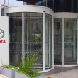 Постер, плакат: Street signage board with Toyota logo Modern office building Editorial 3D rendering