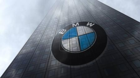 BMW logo on a skyscraper facade reflecting clouds. Editorial 3D rendering