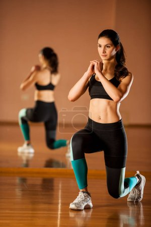 Beautiful fit woman works out in a fitness gym making lunge step