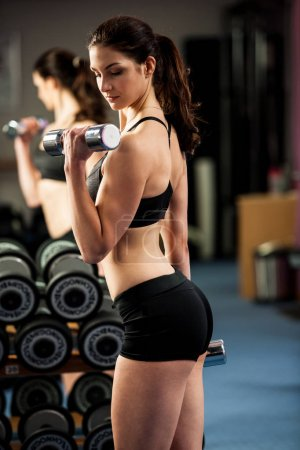 Beautiful fit woman works out with dumbbells in a fitness gym