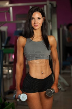 Beautiful sporty woman works out her arms in fitness gym