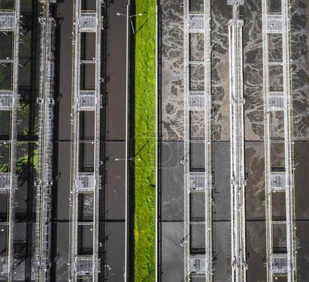 Photo pour Ferme des eaux usées. Photo aérienne statique, regardant vers le bas sur la clarification de citernes et l'herbe verte. Texture de fond géométrique. - image libre de droit