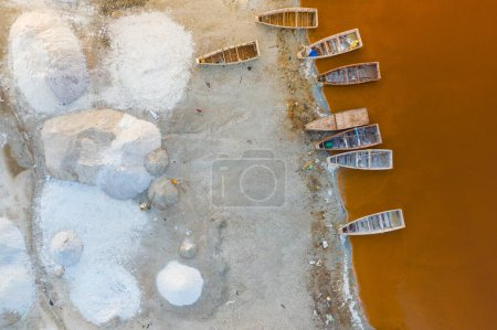 Photo for Aerial view of the small boats for salt collecting at pink Lake Retba or Lac Rose in Senegal. Photo made by drone from above. Africa Natural Landscape. - Royalty Free Image