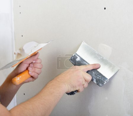 repairman works with plasterboard