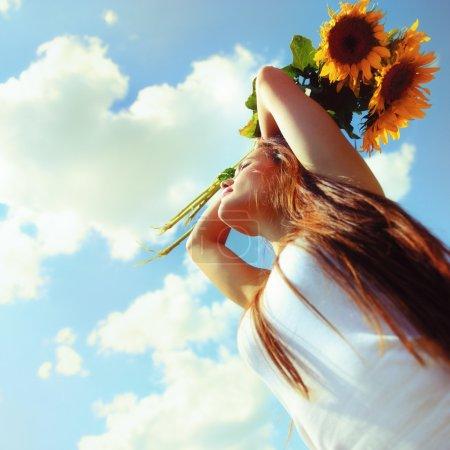 Beautiful woman holding sunflowers