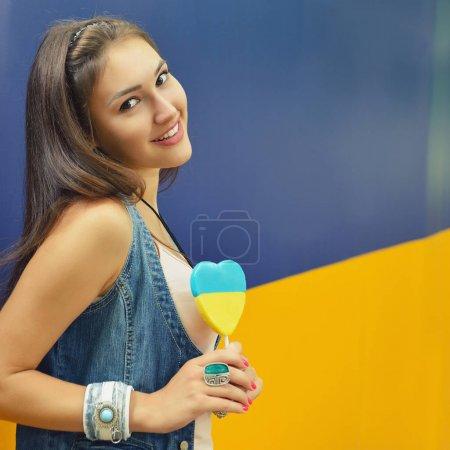 Photo pour Jeune femme joyeuse tenant des bonbons peints aux couleurs du drapeau ukrainien - image libre de droit