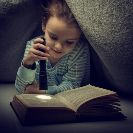 Photo pour Petite fille lisant livre de contes de fées sous les couvertures le soir avec lanterne. Enfant mignon jouant avant d'aller dormir, image tonique . - image libre de droit