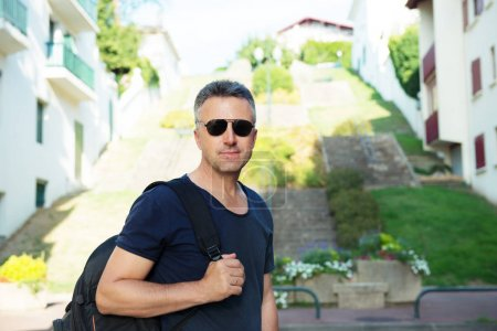 Photo for Male outdoor street portrait. Mid adult man walking at summer city Saint Jean de Luz streets, France. - Royalty Free Image