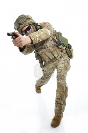 Photo for Military man in camouflage uniform, armor vest, dark glasses and helmet with gun aiming at the enemy, isolated on white background - Royalty Free Image