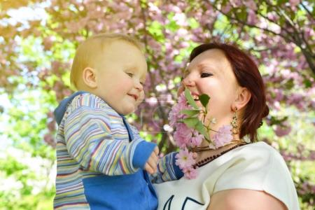 Photo for Happy mother holding her adorable little son. Family outdoor leisure. Little kid with his mom playing in park under the canopy of cherry blossoms, image toned. - Royalty Free Image