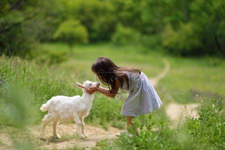 Pequeña niña juega y huhs cabra en el país, primavera o verano