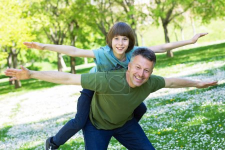 Photo for Portrait of father with his son having fun in summer park. Piggyback. Family fun. Happy boy playing with dad summer nature outdoor - Royalty Free Image