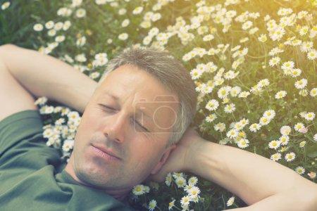 schöner glücklicher lächelnder Mann mittleren Alters liegt auf der Sommerwiese gr
