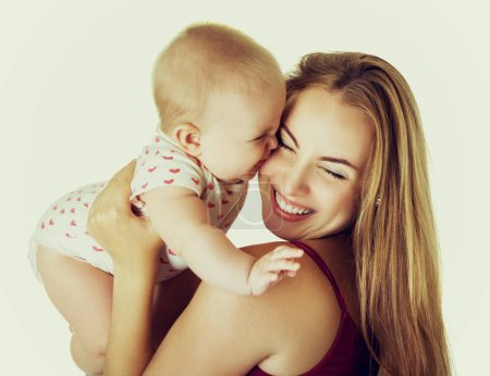 Photo for Young mother with her baby daughter happy smiling, studio portrait, image toned and noise added. Kiss. - Royalty Free Image