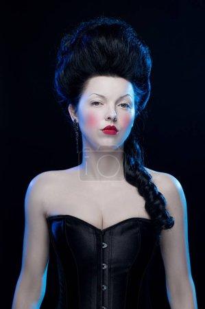 actrice brune femme aux cheveux hauts et un corset à l'ancienne