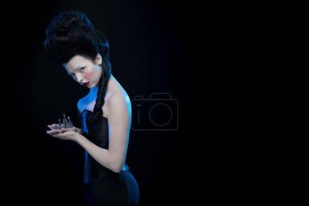 femme brune aux cheveux hauts, une tiare et un corset à l'ancienne