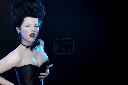 portrait de l'actrice brune aux cheveux hauts, un col noir avec des roses sur le cou et dans un corset à l'ancienne