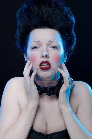 portrait de l'actrice brune aux cheveux hauts, des colliers noirs avec des roses sur le cou et dans un corset à l'ancienne