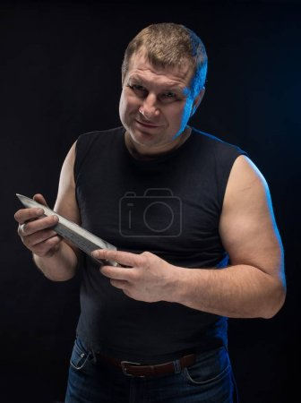 Brutal male actor in black clothes with a knife on a black background. Caricature change.