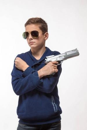 Actor brunette teenager boy in dark glasses with a gun on a white background